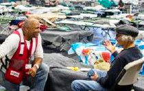 Photo of Red Cross volunteer helping a client in a shelter