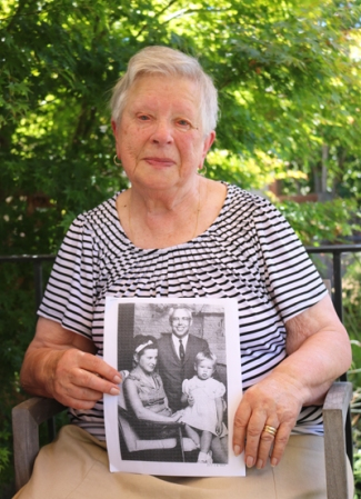 Photo of Tamara holding a photo of her as a child with her parents.